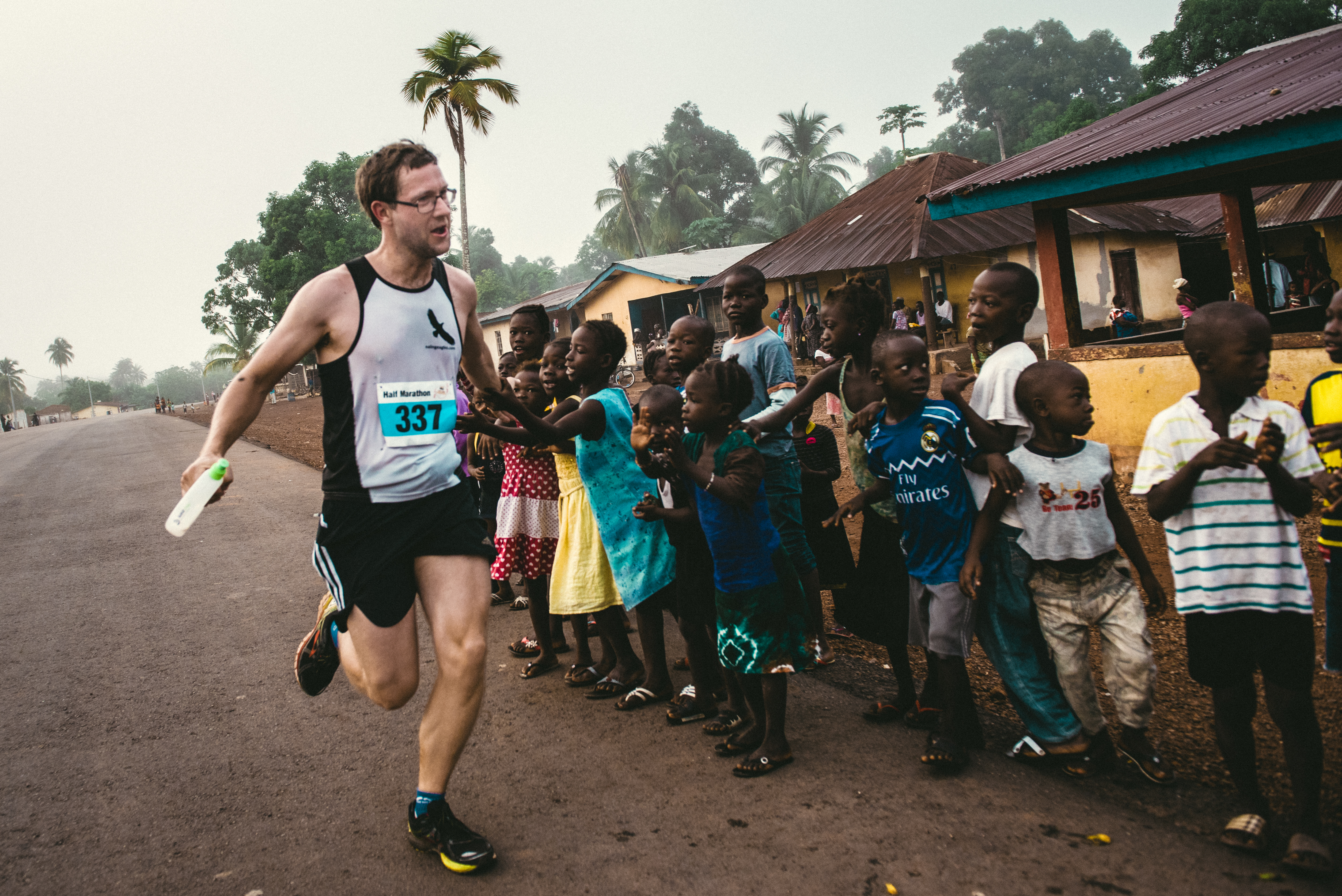 Andy high-fives children while running